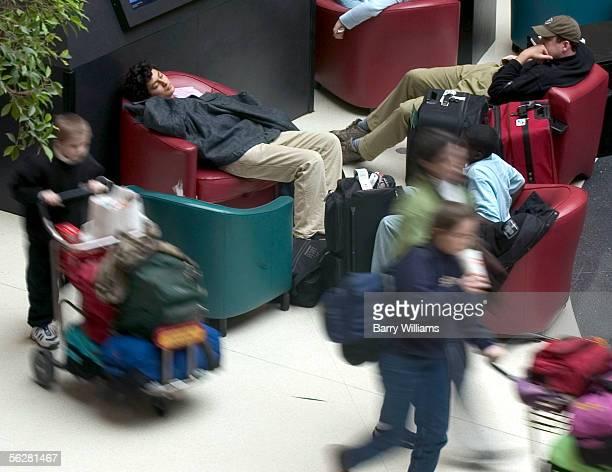 Ricardo Calderon upper left naps while waiting for a bus ride back to school in Atlanta's HartsfieldJackson International Airport November 27 2005 in...