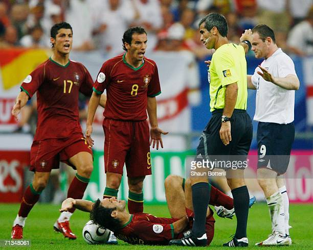 Ricardo Carvalho of Portugal lies on the pitch in pain following a stamp by Wayne Rooney of England as the Portuguese players appeal to Referee...
