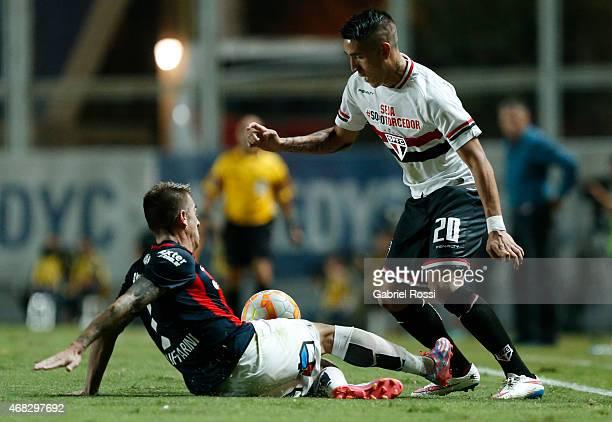 Ricardo Centurion of Sao Paulo fights for the ball with Julio Buffarini of San Lorenzo during a match between San Lorenzo and Sao Paulo as part of...