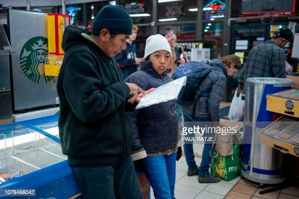 Ricardo ChubBo and his daughter Rosa Maria from Poptun in El Petun department Guatemala are pictured inside of a gas station which acts as a...