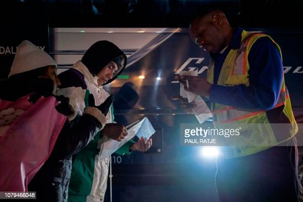 Ricardo ChubBo and his daughter Rosa Maria from Poptun in El Petun department Guatemala show to the Greyhound bus driver their tickets before their...