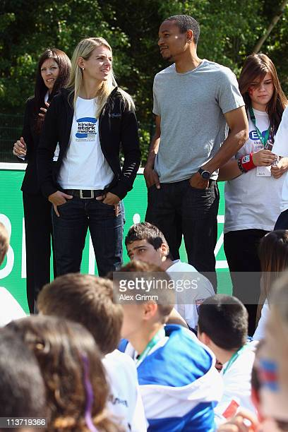 Ricardo Clark of Eintracht Frankfurt chats with Nia Kuenzer during the presentation of a DFB Mini Soccer Field at FriedrichFroebelSchule on May 5...