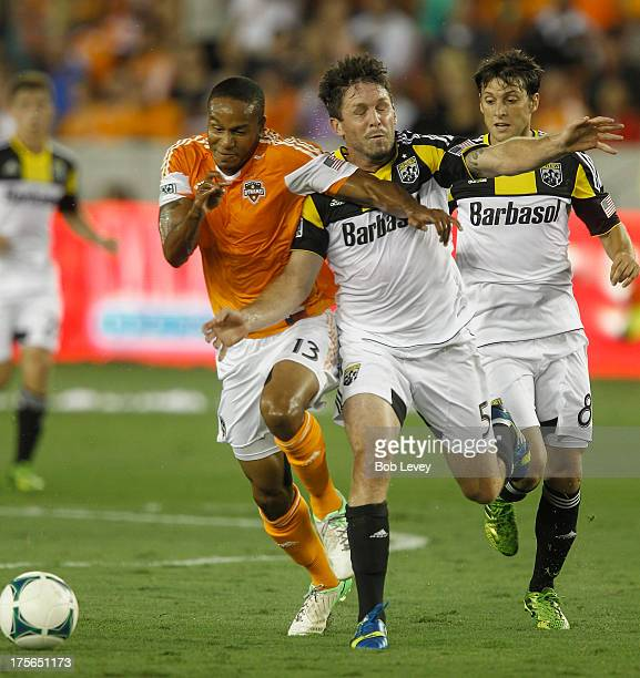 Ricardo Clark of Houston Dynamo holds off Danny O'Rourke of Columbus Crew as he goes for the ball at BBVA Compass Stadium on August 3 2013 in Houston...