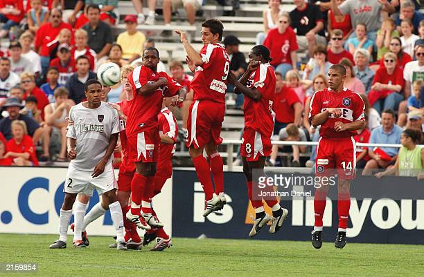 Ricardo Clark of the NY/NJ MetroStars watches the ball as Andy Williams Ante Razov Damani Ralph and Chris Armas of the Chicago Fire jump to block the...