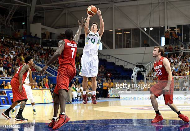 Ricardo Fischer of Brazil scores on a jumper in front of Andrew Nicholson and Brady Heslip of Canada in the gold medal men's basketball during the...