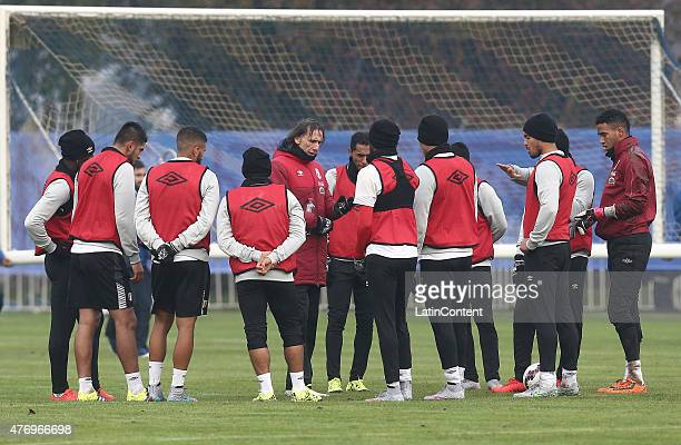 Ricardo Gareca of Peru talks to his players during a training session prior to the debut match against Brazil at Universidad de La Frontera on June...