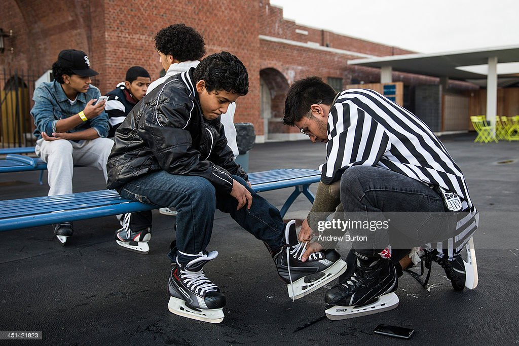 Ricardo Hernandez (R), a supervistor at the Ice Rink at McCarren Pool, helps tie the ice skates of a boy, on November 22, 2013 in the Green Point neighborhood of the Brooklyn borough of New York City. McCarren Pool originally opened in 1936, though it closed in 1984; it reopened in 2012 after a multimillion dollar remodeling. The winter ice rink was unable to open last winter due to complications; this year it is scheduled to stay open through January 5th, 2014.