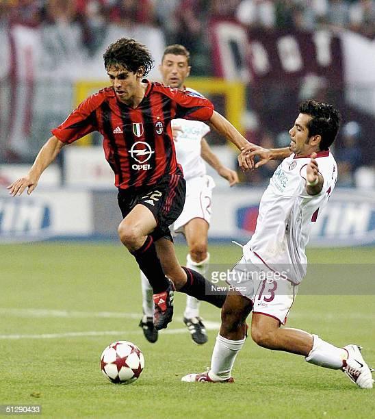 Ricardo Kaka of Milan pushes past Jose Vargas of Livorno during the Serie A match between AC Milan and Livorno at the San Siro stadium on September...