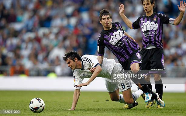 Ricardo Kaka of Real Madrid is tackled by Victor Perez of Valladolid during the La Liga match between Real Madrid and Valladolid at Estadio Santiago...