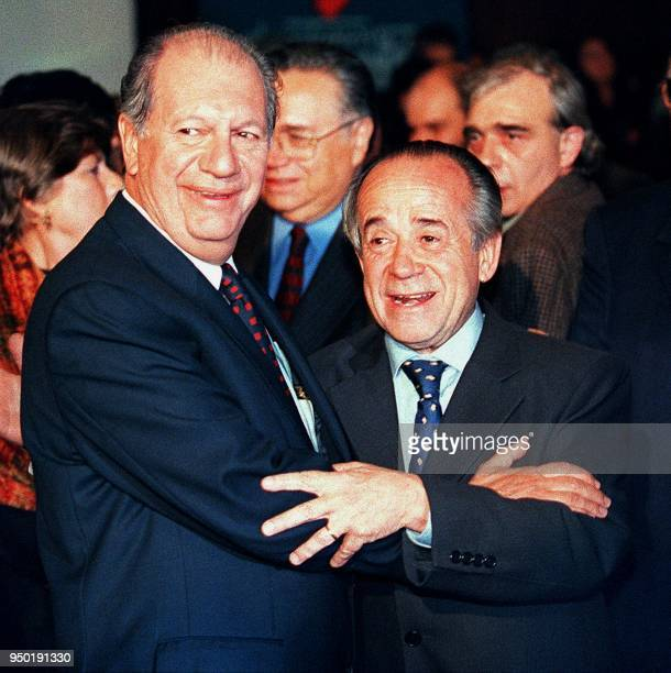 Ricardo Lagos Escobar a presidential candidate for a coalition of Chilean socialist parties hugs his opponent Senator Andres Zaldivar Larrain of the...