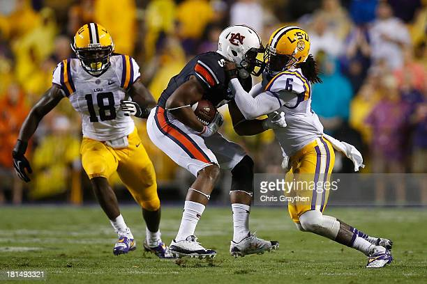 Ricardo Louis of the Auburn Tigers is tackled by Craig Loston of the LSU Tigers at Tiger Stadium on September 21 2013 in Baton Rouge Louisiana