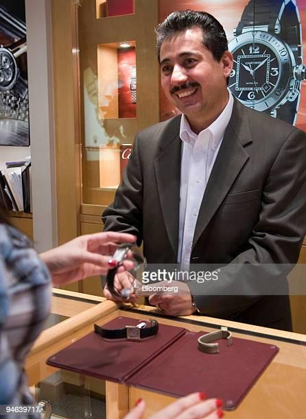 Ricardo Ojeda a salesman at Deutsch Deutsch Jewelers shows Cartier watches to a customer at the La Plaza Mall in McAllen Texas on December 12 2006