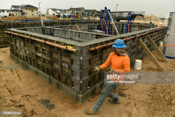 Ricardo Perez straightens out rebar to put into concrete in the foundation of a new home in the Beeler Park neighborhood of Stapleton on August 1 in...
