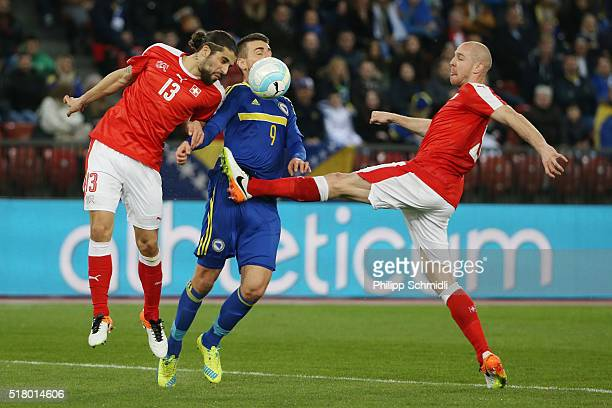 Ricardo Rodriguez and Philippe Senderos of Switzerland fight for the ball with Vedad Ibisevic of BosniaHerzegovina during the international friendly...