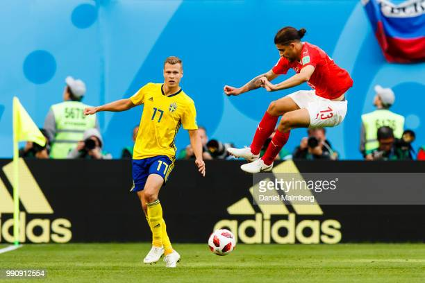 Ricardo Rodriguez of Switzerland jumps over the ball with Viktor Claesson of Sweden at his side during the 2018 FIFA World Cup Russia Round of 16...