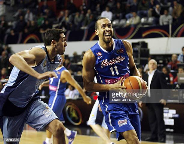Ricardo Sanchez of Puerto Rico carries the ball past Gustavo Barrera of Uruguay during a qualifying round match of the 2011 FIBA Americas...