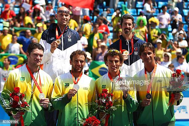 Ricardo Santos Emanuel Rego Marcio Araujo and Fabio Magalhaes of Brazil along with Philip Dalhausser and Todd Rogers of the United States hold their...