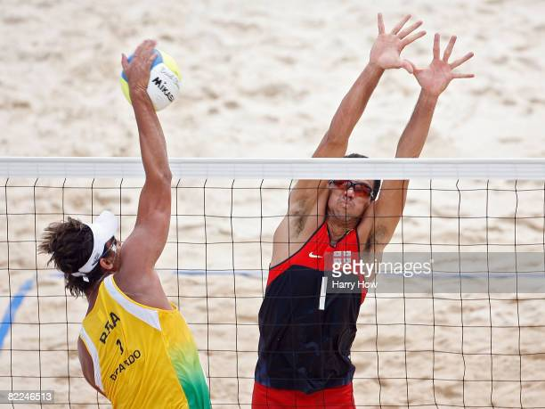 Ricardo Santos of Brazil spikes the ball against Jorge Terceiro of Georgia during the beach volleyball event at the Chaoyang Park Beach Volleyball...