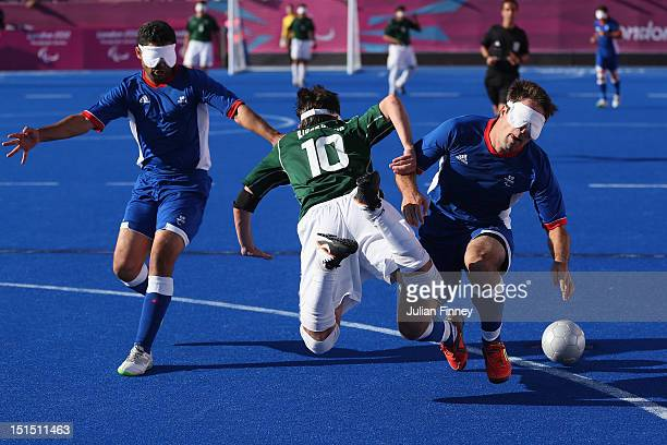 Ricardo Steinmetz Alves of Brazil clashes with David Labarre and Abderrahim Maya of France in the gold medal match during the 5 aside Football on day...