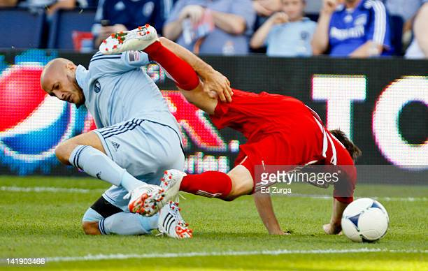 Ricardo Villar of the FC Dallas falls over Aurelien Collin of the Sporting Kansas City as they vie for the ball in the first half at Livestrong...