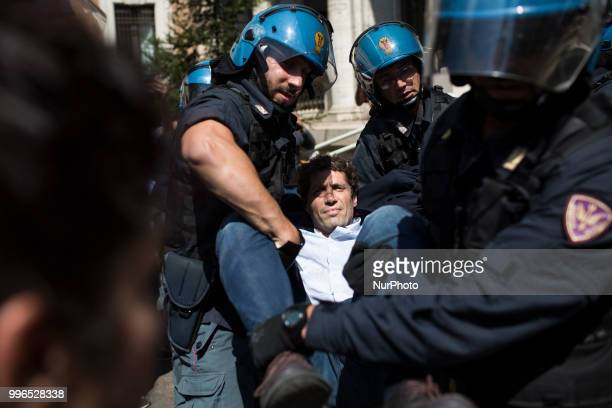 Riccardo Magi national secretary of the Italian Radicals is dragged away by Italian police outside the Ministry of Transport in Rome on July 11 2018...