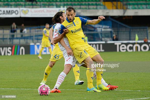 Riccardo Meggiorini of Chievo Verona competes with Cristian Zaccardo of Carpi FC during the Serie A match between AC Chievo Verona and Carpi FC at...