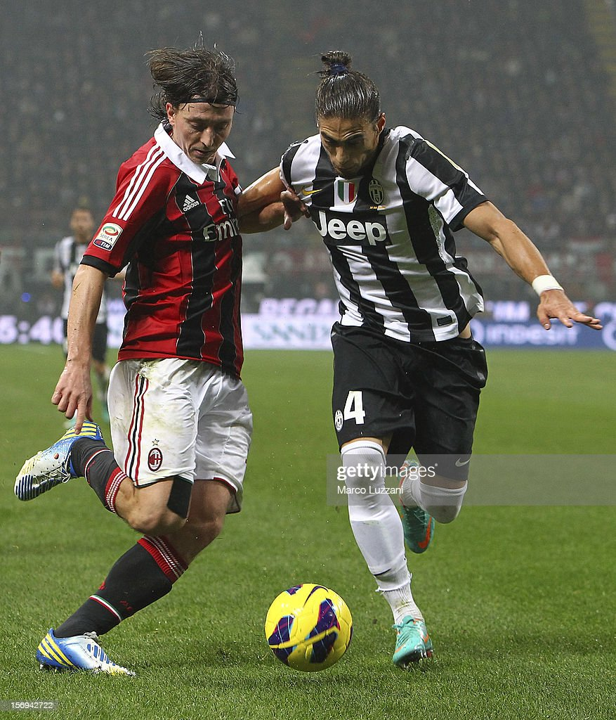 Riccardo Montolivo of AC Milan competes for the ball with Martin Caceres of Juventus FC during the Serie A match between AC Milan and Juventus FC at San Siro Stadium on November 25, 2012 in Milan, Italy.