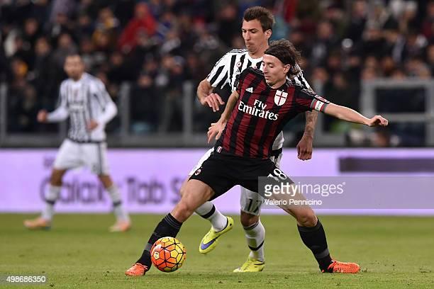 Riccardo Montolivo of AC Milan is challenged by Mario Mandzukic of Juventus FC during the Serie A match between Juventus FC and AC Milan at Juventus...