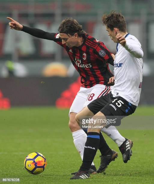 Riccardo Montolivo of AC Milan is challenged by Marten De Roon of Atalanta BC during the serie A match between AC Milan and Atalanta BC at Stadio...