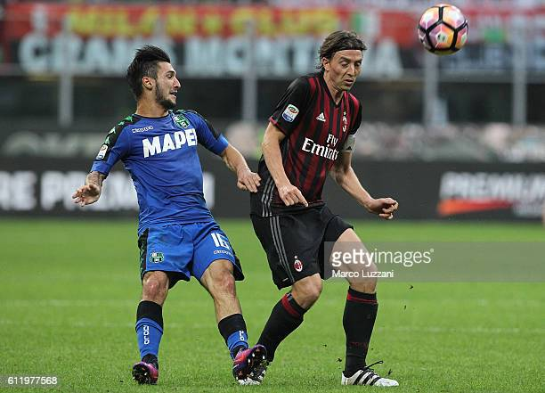 Riccardo Montolivo of AC Milan is challenged by Matteo Politano of US Sassuolo during the Serie A match between AC Milan and US Sassuolo at Stadio...