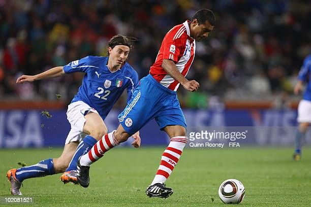 Riccardo Montolivo of Italy chases Paulo Da Silva of Paraguay during the 2010 FIFA World Cup South Africa Group F match between Italy and Paraguay at...