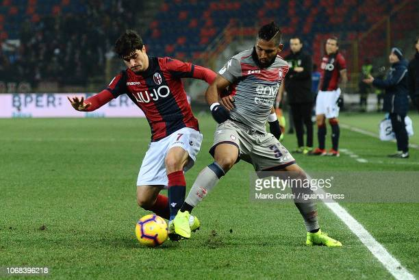 Riccardo Orsolini of Bologna FC competes for the ball against Aristóteles Romero of Crotone FC during the Coppa Italia match between Bologna FC and...
