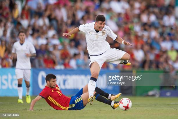Riccardo Orsolini of Italy is tackled by Aaron Niquez of Spain during the Italy v Spain Under21 Friendly match at Estadio Municipal Salta del Caballo...