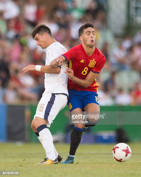 Riccardo Orsolini of Italy is tackled by Mikel Merino of Spain during the Italy v Spain Under21 Friendly match at Estadio Municipal Salta del Caballo...