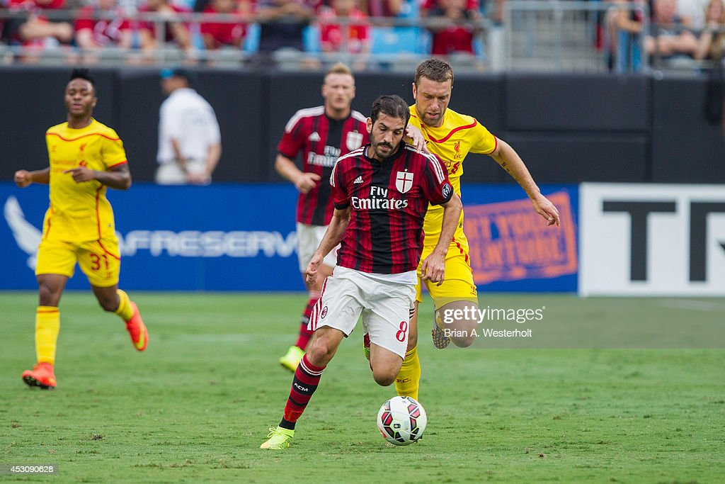 Riccardo Saponara #8 of A.C. Milan is grabbed from behind by Rickie Lambert #9 of Liverpool in the Guinness International Champions Cup at Bank of America Stadium on August 2, 2014 in Charlotte, North Carolina. Liverpool defeated A.C. Milan 2-0.
