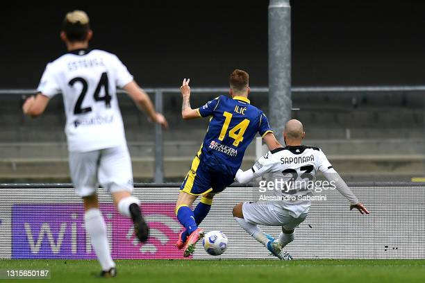 Riccardo Saponara of Spezia Calcio scores their side's first goal whilst under pressure from Ivan Ilic of Hellas Verona during the Serie A match...