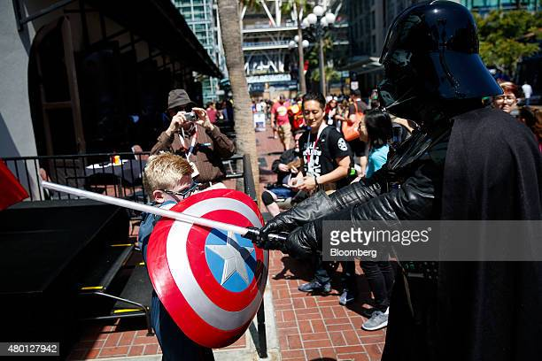 Ricci Tomasello dressed as Marvel Comics' Captain America left battles with Darth Vader from the Star Wars franchise during the ComicCon...