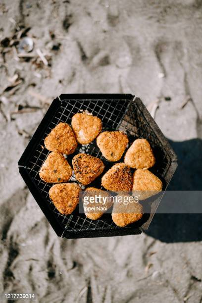 rice balls on barbecue grill on beach - rice ball stock pictures, royalty-free photos & images