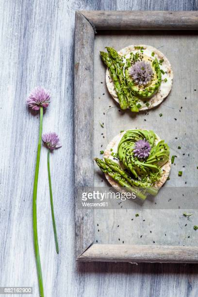 Rice cakes with cream cheese, avocado and asparagus garnished with black cumin seeds and chive blossom