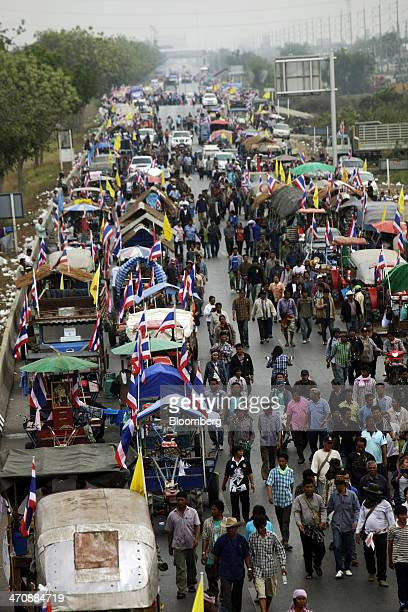 Rice farmers walk alongside trucks to block a highway during a protest in Bang PaIn Ayutthaya province Thailand on Friday Feb 21 2014 Prime Minister...