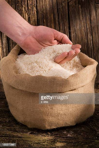 Rice grains in a jute bag with hand