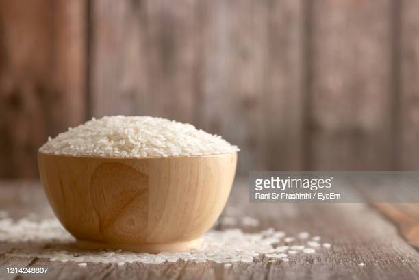 rice in a brown bowl on the wooden table with blurred background - 米 ストックフォトと画像