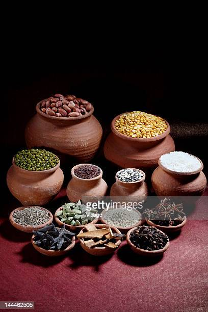 rice, nuts, spices and pulses in earthen pots - garam masala stock photos and pictures