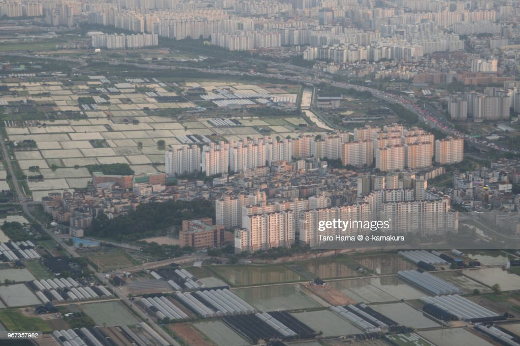 Rice paddy and many apartments in Incheon city in Korea sunset time aerial view from airplane : ストックフォト