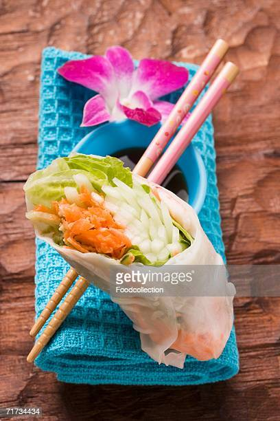 Rice paper roll with soy sauce, chopsticks and orchid
