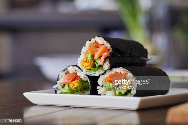 rice roll wrapped in a plate. - maki sushi stock pictures, royalty-free photos & images