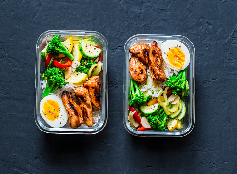 Rice, stewed vegetables, egg, teriyaki chicken - healthy balanced lunch box on a dark background, top view. Home food for office concept 1007313694