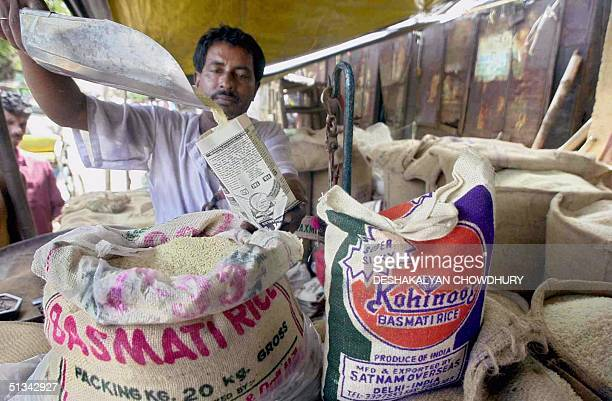 Rice vendor Ratan Das fills a small paper packet with Basmati rice in Calcutta 23 August 2001 The Indian government attempted to quell the uproar...