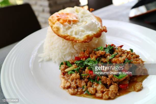 rice with spicy fried pork with basil leaves and fried egg on white plate. thai style food. - aungsumol stock pictures, royalty-free photos & images