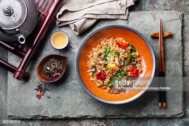Rice with vegetables in red bowl and green tea on stone slate ba